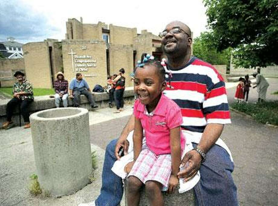 Chris Williams and his 4-yearo ld daughter, Crystal, of New Haven, enjoy the Freddie Fixer Parade along Dixwell Avenue Sunday. (Peter Casolino/Register)