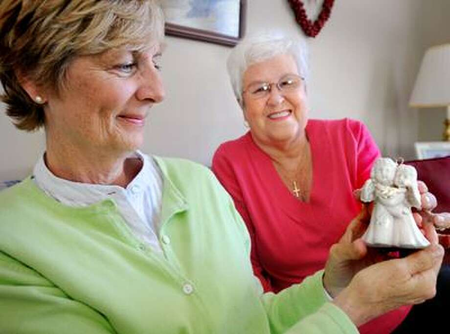 Pam Lunn (L) and her sister in law, Rosanna Chidsey in Chidsey's Madison home. Lunn gave Chidsey one of herher kidneys.  She is holding an ornament that speaks to their special relationship. (Melanie Stengel/Register)
