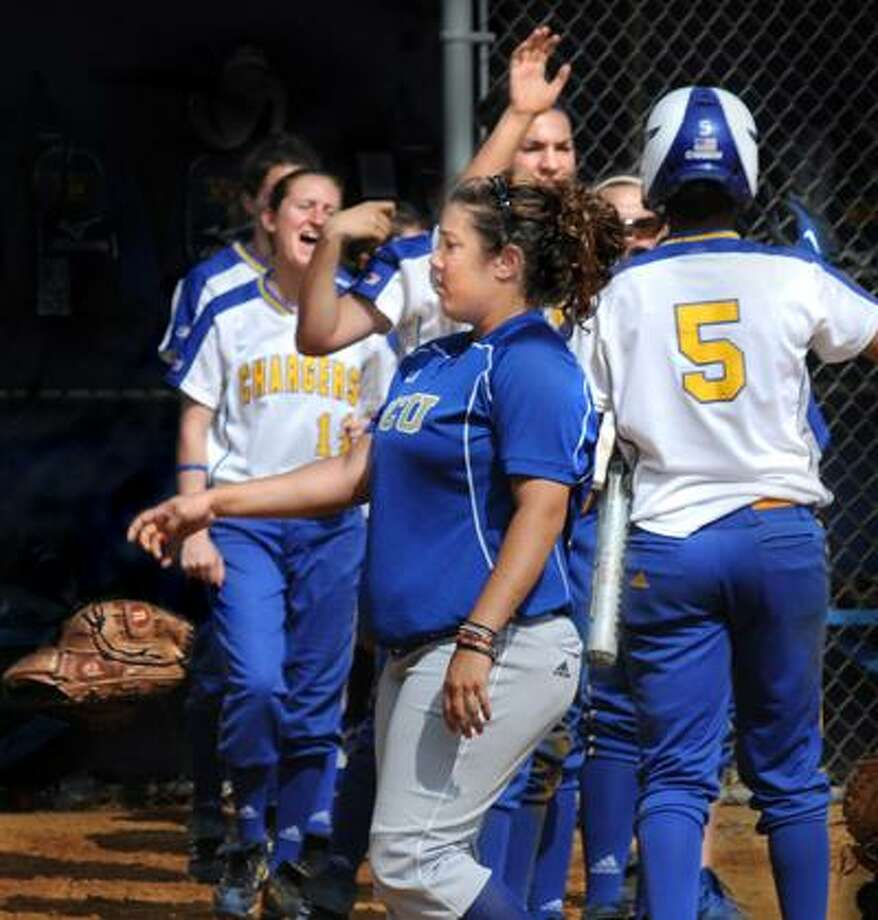 Georgian Court pitcher Diana Sansevera tosses her glove as Christina Gelardi (5) is welcomed home by teammates after scoring to give New Haven an 8-0 lead. The eighth run resulted in a mercy-rule victory, and the Chargers will face Southern Connecticut State today at 11 a.m. (Melanie Stengel/Register)