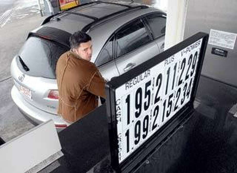 Anthony Phillips of Boston watches the meter as he fills his gas tank at the Woodmont Shell Station along Old Gate Lane in Milford. (Peter Casolino/Register)