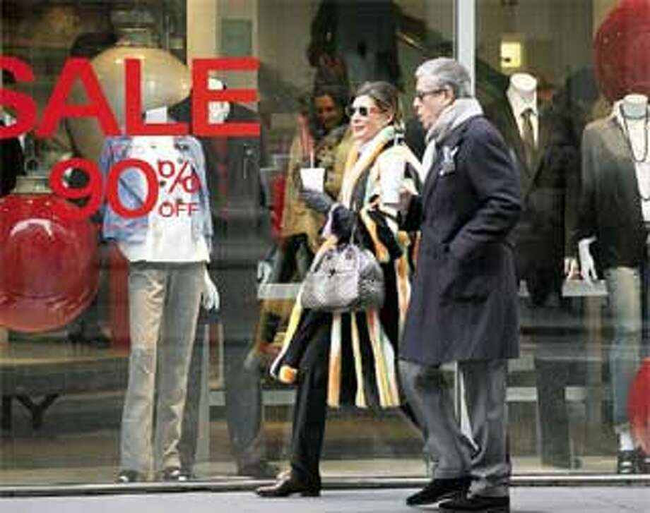 Shoppers on New York's Madison Avenue pass a clothing store promoting a sale of up to 90 percent off. Consumer spending fell for a record sixth straight month in December, the Commerce Department said Monday. (Associated Press photos)