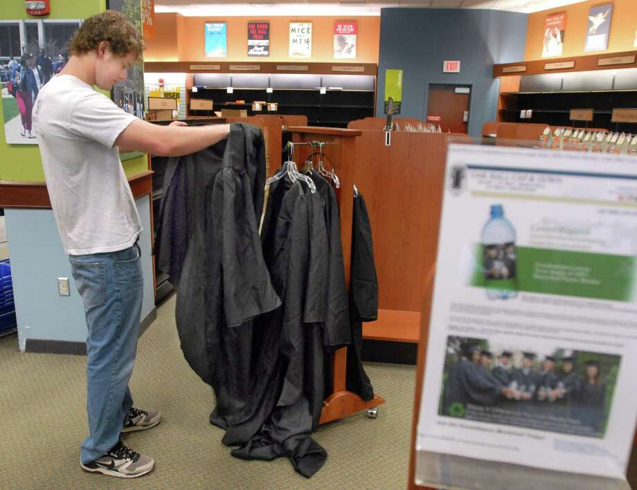 SCSU graduating senior Ian Crandall of Gales Ferry already has his gown but had not tried it on yet. He tried on gowns on display at the SCSU bookstore to check size. The gowns at SCSU are made from recycled plastic bottles.  Photo by Mara Lavitt