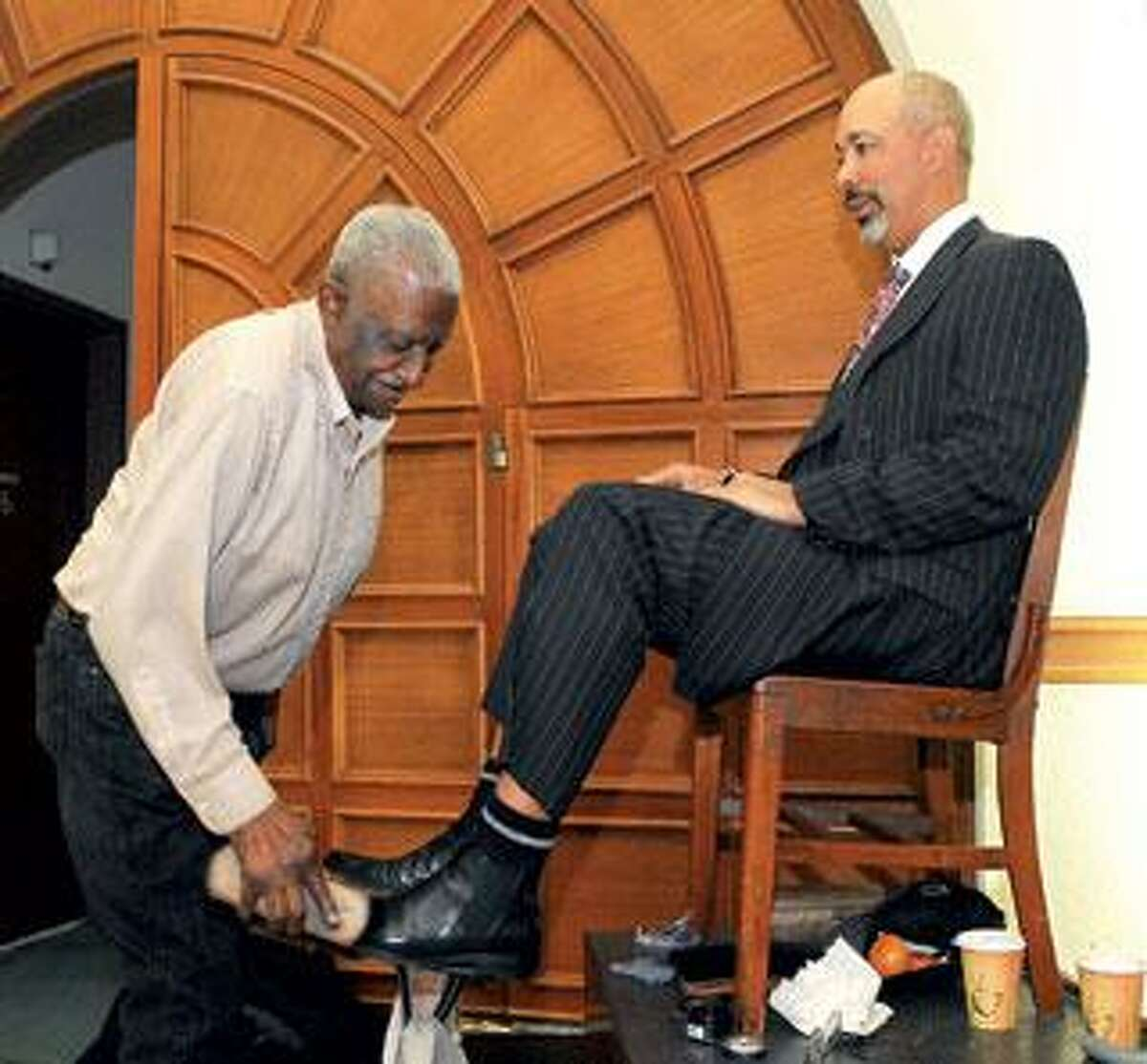 Vincent Williams shines the shoes of Attorney Gerald Harmon in the lobby of 59 Elm St. in New Haven. (Peter Casolino/Register)