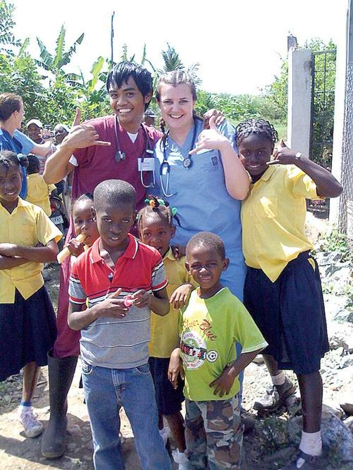 Quinnipiac University physician-assistant graduate students Ryan Narciso of Hamden and Carolyn Allen with children from Pancho Mateo in the Dominican Republic. Contributed photo