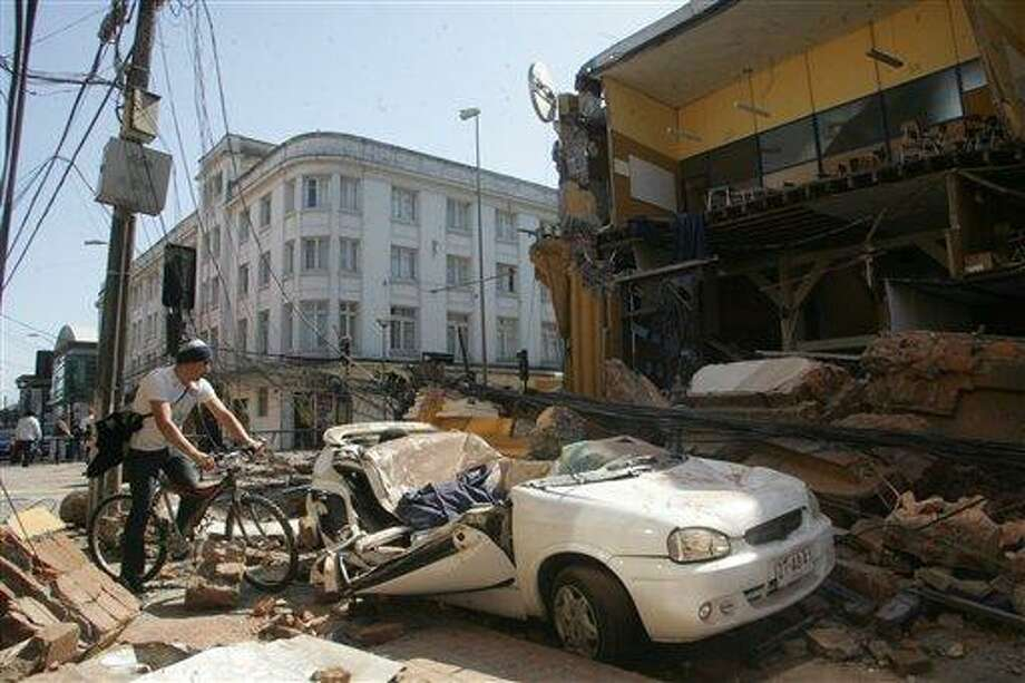 A man rides his bicycle along a destroyed building in Concepcion, Chile, Saturday Feb. 27, 2010 after an 8.8-magnitude struck central Chile. The epicenter was 70 miles (115 kilometers) from Concepcion, Chile's second-largest city.(AP Photo) Photo: ASSOCIATED PRESS / AP2010