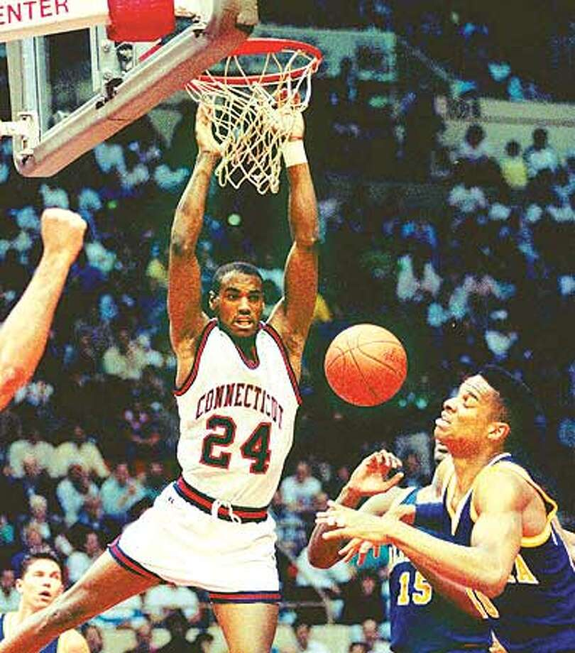 Scott Burrell of the University of Connecticut dunks the ball past Byrant Walton, right, and Brian Hendrick (15) of the University of California in the UConn-California game in the second round of the NCAA East Regional playoffs in Hartford, Conn., Saturday, March 17, 1990. (AP Photo/Bob Child)