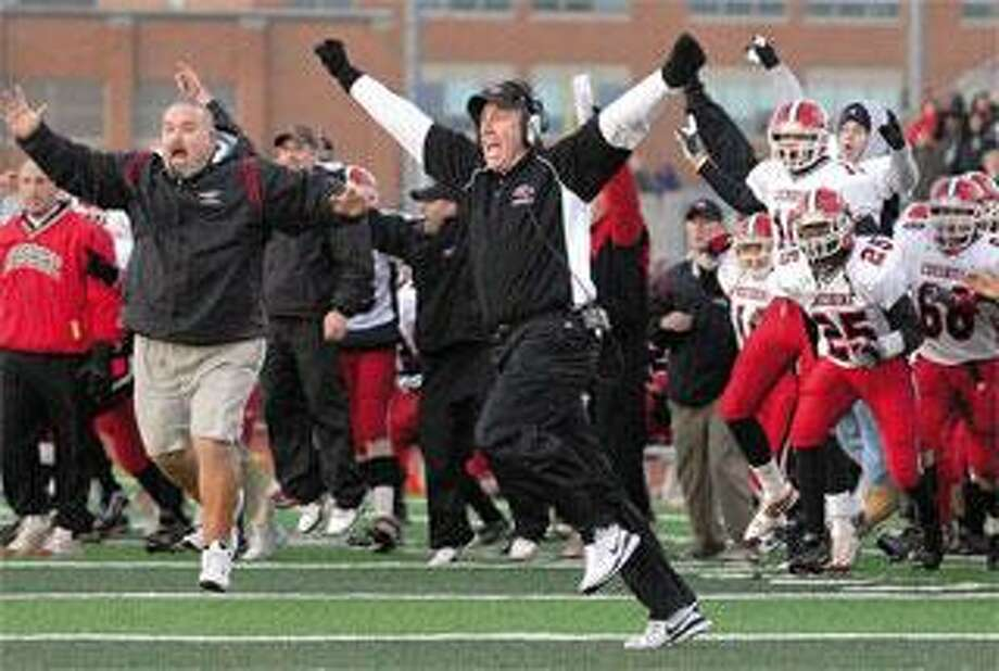 CHESHIRE FOOTBALL COACH MARK ECKE, center, jumps for joy after Staples lost the ball on a fumble in overtime, giving the Rams a 28-21 win in the Class LL state championship game Sunday in West Haven. (Peter Casolino/Register)