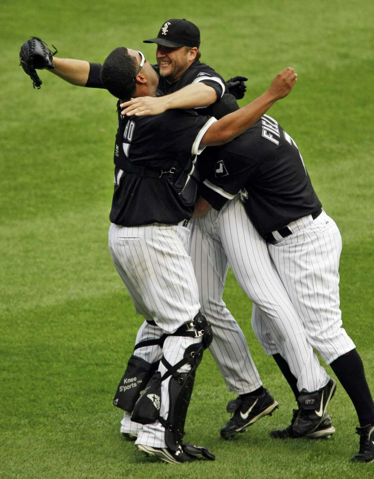 Chicago White Sox pitcher Mark Buehrle, center, is embraced by teammates Josh Fields, right, and Ramon Castro, after Buehrle threw a perfect game against the Tampa Bay Rays in a baseball game, Thursday(AP Photo/Chicago Tribune, Phil Velasquez)