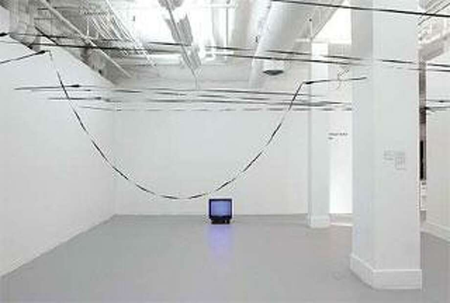 """""""Play/Pause,"""" metal armature, aluminum arrow shafts, blank VHS videotape, television monitor and VCR player on pause. (William Lamson)"""