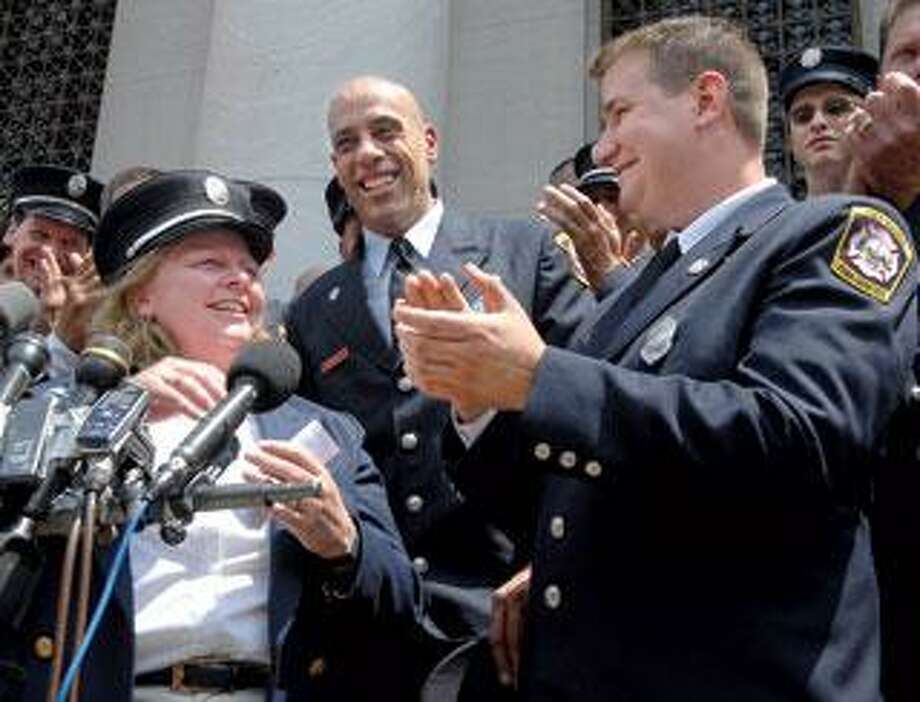 Karen Torre puts on a firefighter's hat last month after the U.S. Supreme Court ruled in favor of a group of New Haven firefighters who claimed reverse discrimination. (Brad Horrigan/Register file photo)