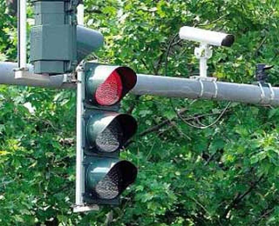 Cameras to record motorists running red lights may soon join the video cameras already mounted next to street lights at many city intersections, such as this one at Sargent Drive and Church Street Extension. (Register file photo)
