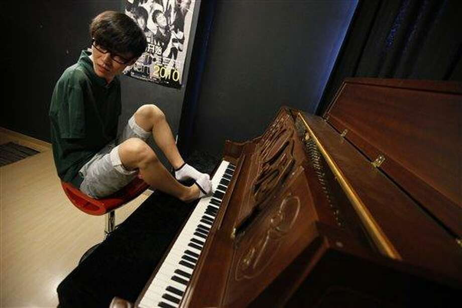 "FILE - In this Aug. 26, 2010 file photo, pianist Liu Wei takes off one of his socks to play a piano before his practice session in Shanghai.  The musician who lost both arms in a childhood accident and plays the piano with his toes won ""China's Got Talent,"" performing his version of James Blunt's wistful lovesong ""You're Beautiful"" to a packed audience at the Shanghai Stadium, on Sunday, Oct. 10, 2010.  (AP Photo/Eugene Hoshiko, File) Photo: AP / AP"