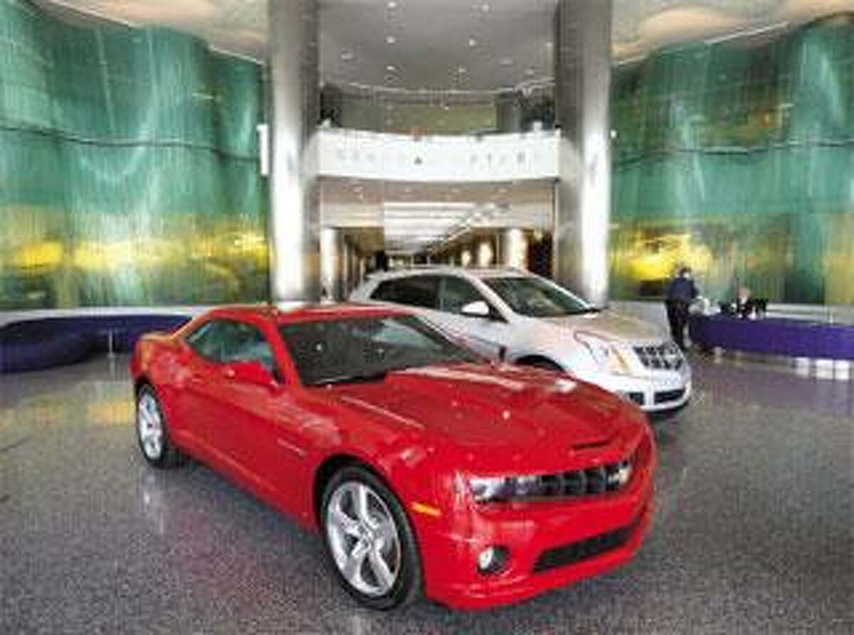 A Camaro, foreground, and a Cadillac SRX are seen inside the General Motors headquarters in Detroit. On Thursday, a judge's order allowing General Motors to sell most of its assets to a new company went into effect. (Associated Press)