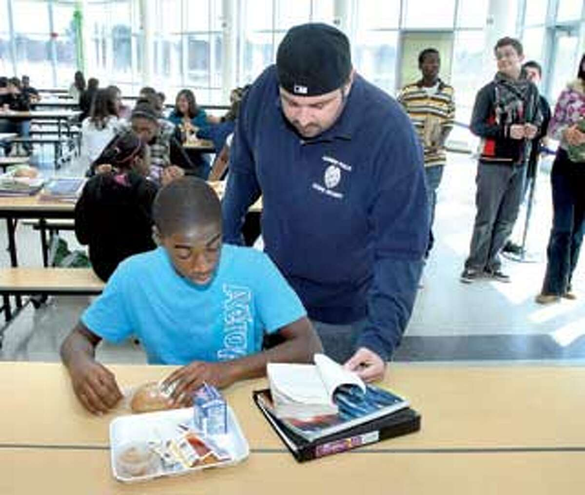 Hamden Middle School security officer Mike Sarno talks with eighth-grader E.J. Okoro, 13, during lunch. The Hamden resident beat acute lymphocytic leukemia. (Arnold Gold/Register)