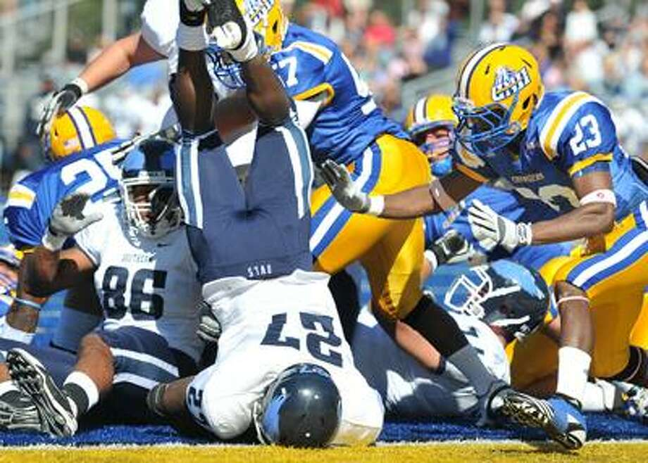 In an unbelievable stand just inches from the goal line, the New Haven defense stops SCSU running back Rashad Slowley (27) as he comes down over the top of the pile. UNH held SCSU on the next play as well. At right is UNH's Bernard Risco. (Peter Casolino/Register)