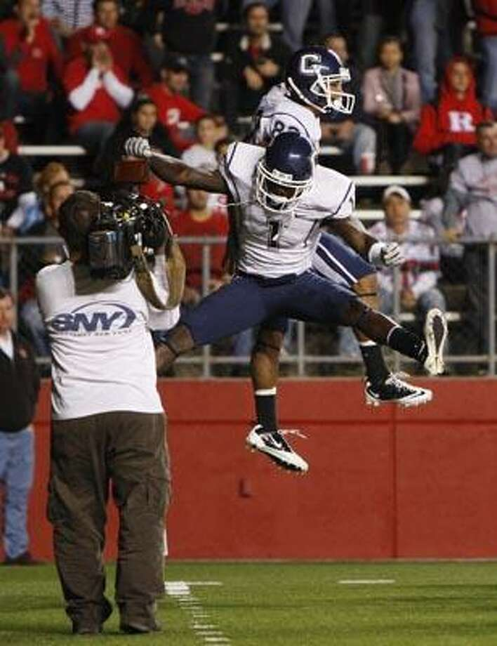 Connecticut's Kashif Moore (82) and Dwayne Difton (1) celebrate in the endzone against Rutgers during the first half of an NCAA college football game in Piscataway, N.J. on Friday, Oct. 8, 2010. (AP Photo/Tim Larsen) Photo: AP / AP