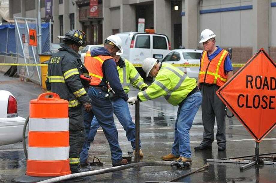 """Cas101006 Peter Casolino  10/06/10New Haven-- Southern CT Gas workers along with New Haven Firefighters work to close off a 6"""" gas main at the corner of Church and Crown Streets after it was severed by construction workers.  Photo/Peter Casolino ***"""