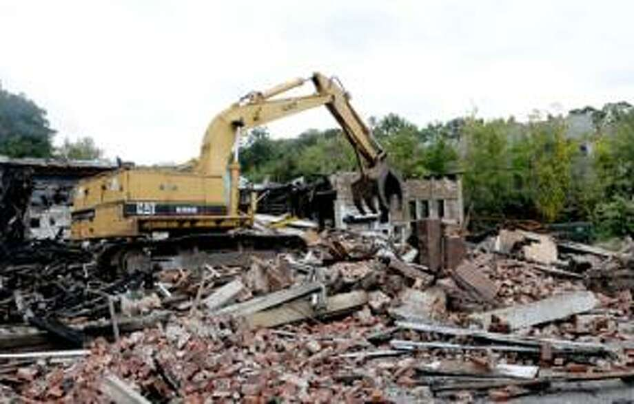 Peter Hvizdak/Register  Demolition takes place Monday at the former Housatonic Wire Co. in Seymour. An accidental fire Sept. 11 swept through the vacant building, which was slated for redevelopment.