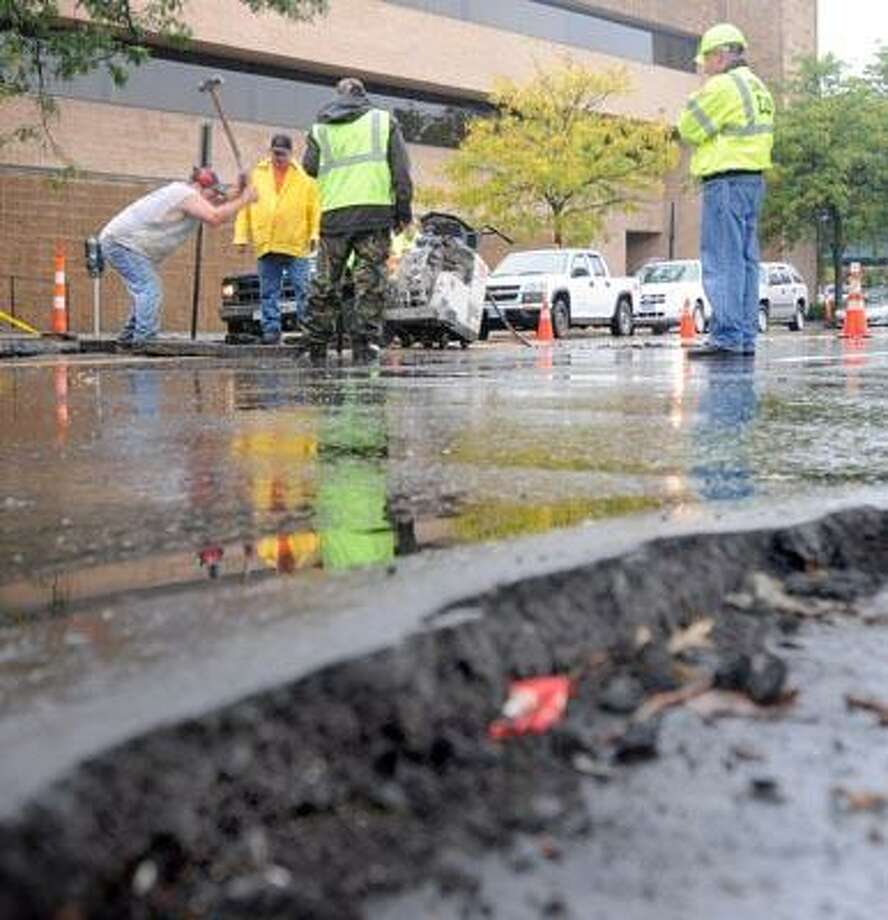 Connecticut DOT, New Haven Public Works Department and a private contractor rip up  the road on Union Ave. in front of the Police department building and near Union Station Friday trying to find the cause of road heaves and flooding on Union Ave. (Peter Hvizdak/Register)
