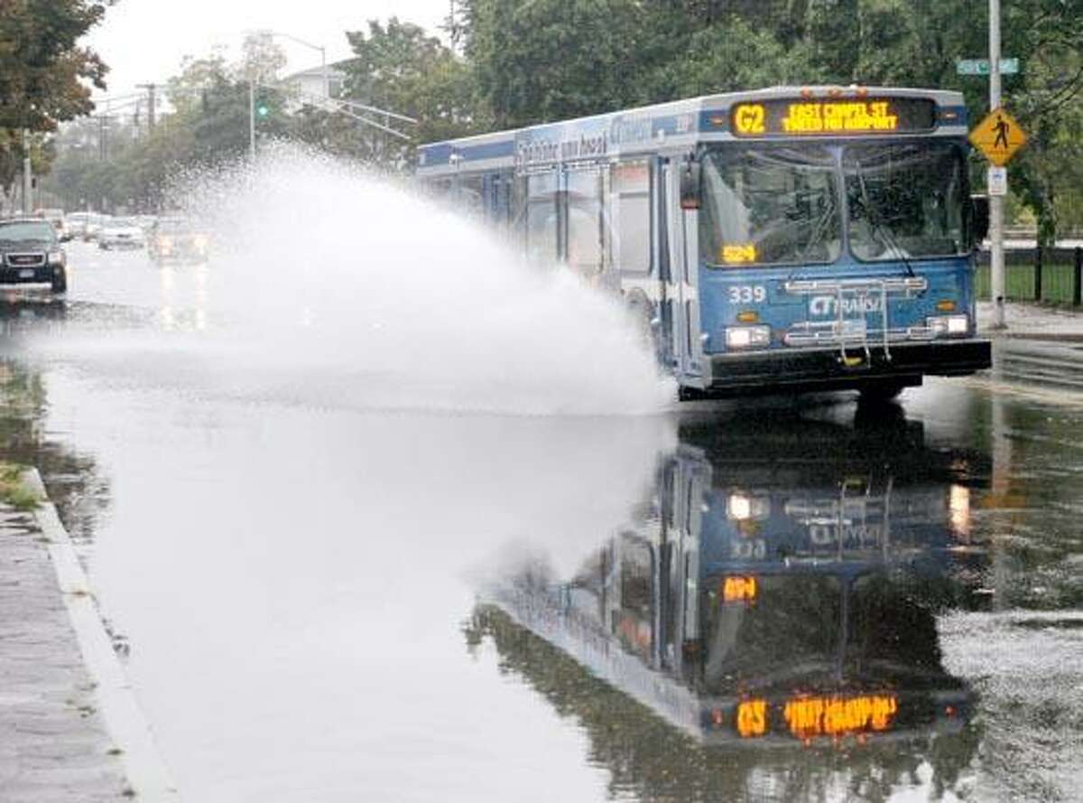 A Connecticut Transit bus throws out a wall of spray as it passes through a large puddle on Dixwell Avenue in New Haven Friday morning. (Peter Hvizdak/Register)