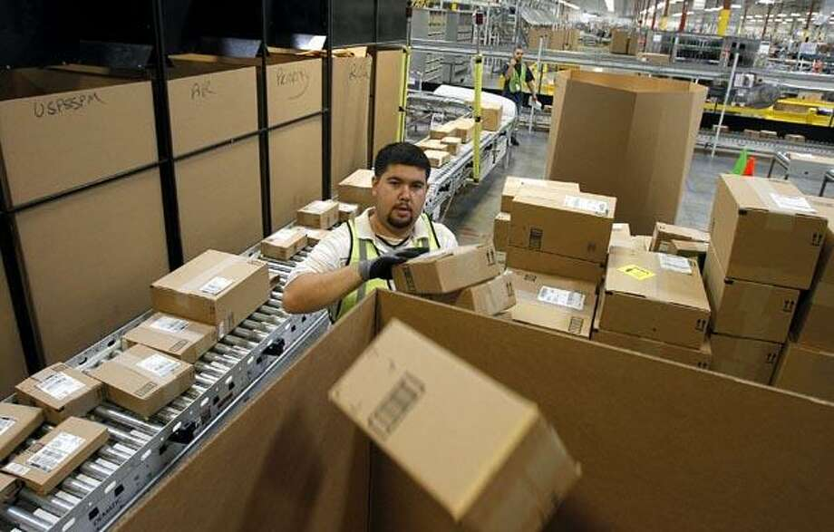 """In this Nov. 11, 2010 photo, Ricardo Sandoval places packages in the right shipping boxes at an <a href=""""http://Amazon.com"""">Amazon.com</a> fulfillment center, in Phoenix. (AP Photo/Ross D. Franklin) Photo: AP / AP"""