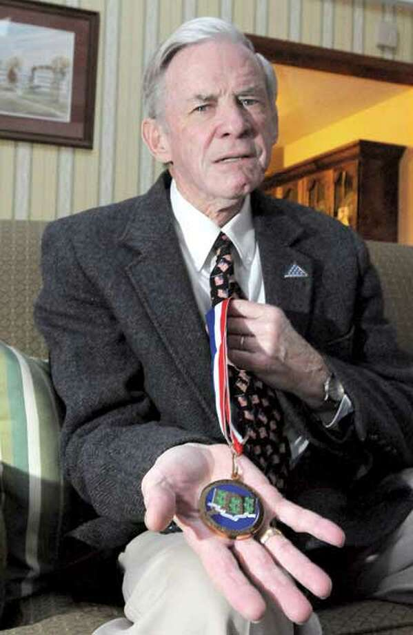 Abner Oakes, a U.S. Navy veteran from Hamden, has been named to the Connecticut Veterans' Wall of Fame. Here, Oakes holds his medal from the ceremony. (Brad Horrigan/Register)
