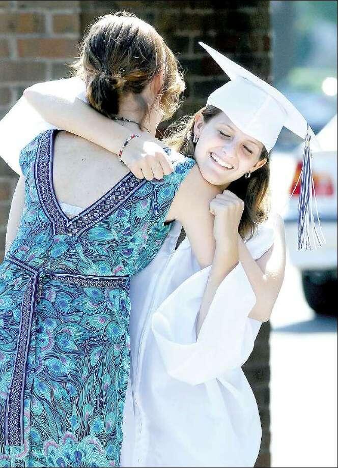 Arnold Gold/Register  Kathryn Mill, left, hugs Emily Miller before graduation ceremonies at Old Saybrook High School Friday.