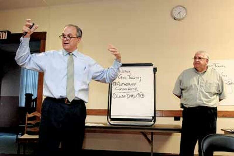Mayor John DeStefano Jr., left, and Amtrak division engineer George Fitter take questions from the audience at Pilgrim Congregational Church Tuesday night. Area residents had a long list of concerns raised by Amtrak's night work in their neighborhood. (Peter Casolino/Register)