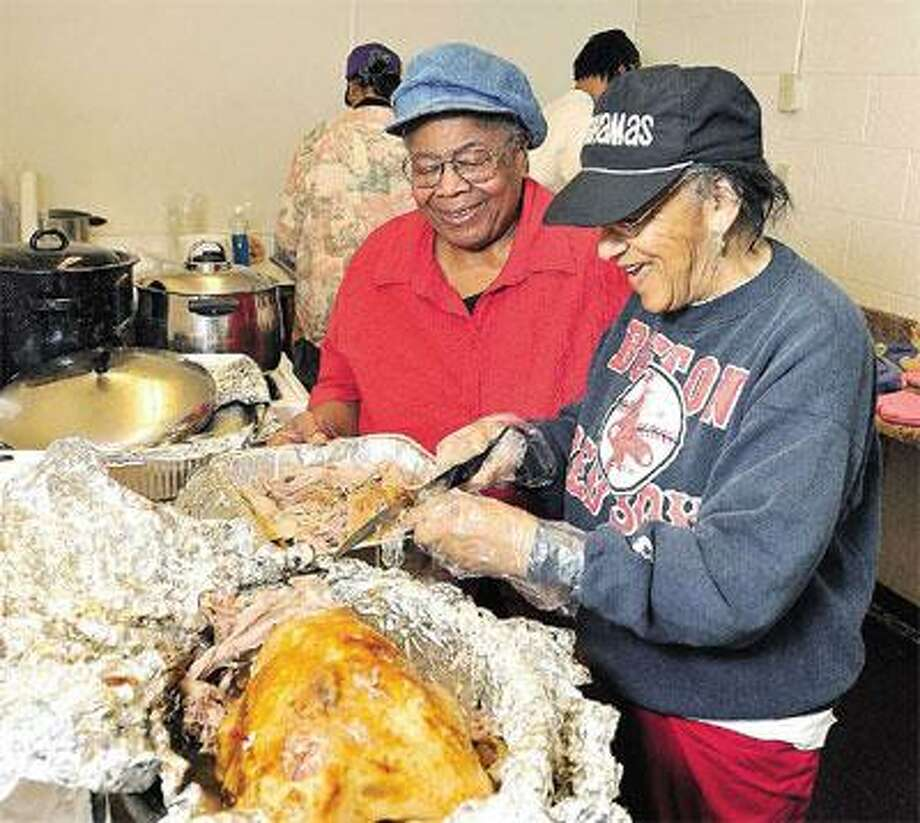 Barbara Murphy, left, and Shirley Bryant, daughters of Elks members, prepare a free Thanksgiving feast at the Elks East Rock Lodge on Dixwell Avenue in New Haven Thursday. LEFT: Volunteer Kenny Brogdon removes a turkey froma deep fryer Thursday for the Elks' dinner. The key to the flavor of fried turkey is the injected marinade and a dry rub, he says. (Peter Casolino/Register)