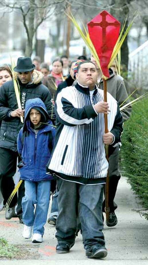 Carlos Claudio, center, of North Haven, leads a Palm Sunday procession of parishioners from St. James Episcopal Church down Quinnipiac Avenue in New Haven Sunday.  (Arnold Gold/Register)