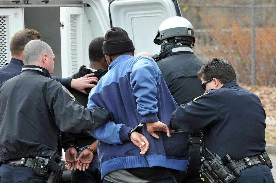 New Haven police prepare to transport several men after they were involved in a fight in the stands at the Hillhouse/Cross football game. Photo by Peter Casolino/New Haven Register