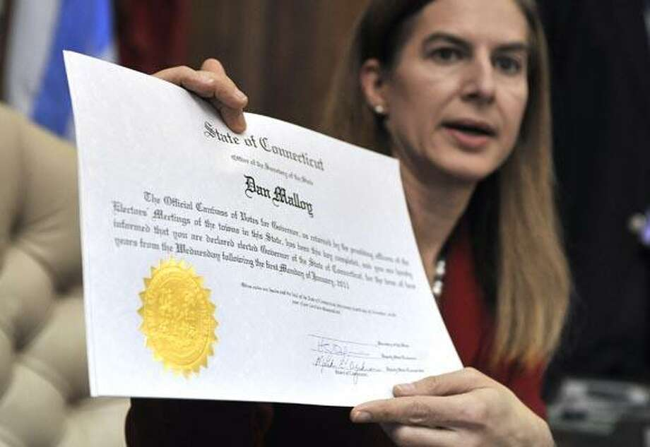 Connecticut Secretary of the State Susan Bysiewicz holds up a certificate she will sign certifying the Nov. 2 election for Governor-elect Dan Malloy her office at the Capitol in Hartford, Conn., Wednesday, Nov. 24, 2010.  (AP Photo/Jessica Hill) Photo: AP / AP2010