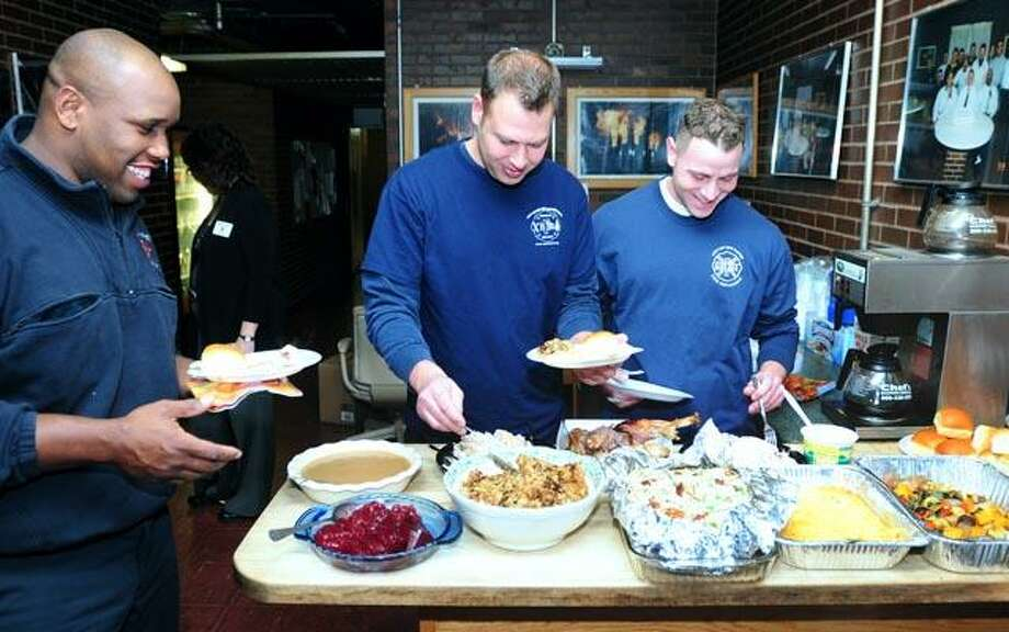 Left to right - Firefighters Edward Taylor, Chick Kranyak and Mike Milano partake of a Thanksgiving dinner brought by the Rotary Club of New Haven to the West Battalion Headquarters in New Haven on 11/24/2010.Photo by Arnold Gold/New Haven Register    AG0394B