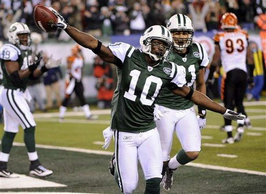 New York Jets wide receiver Santonio Holmes (10) celebrates after scoring a touchdown as teammates Dustin Keller (81) and Tony Richardson (49) and Cincinnati Bengals' Frostee Rucker (92) look on during the third quarter of an NFL football game at New Meadowlands Stadium, Thursday, Nov. 25, 2010, in East Rutherford, N.J.  (AP Photo/Bill Kostroun) Photo: AP / FR59151 AP