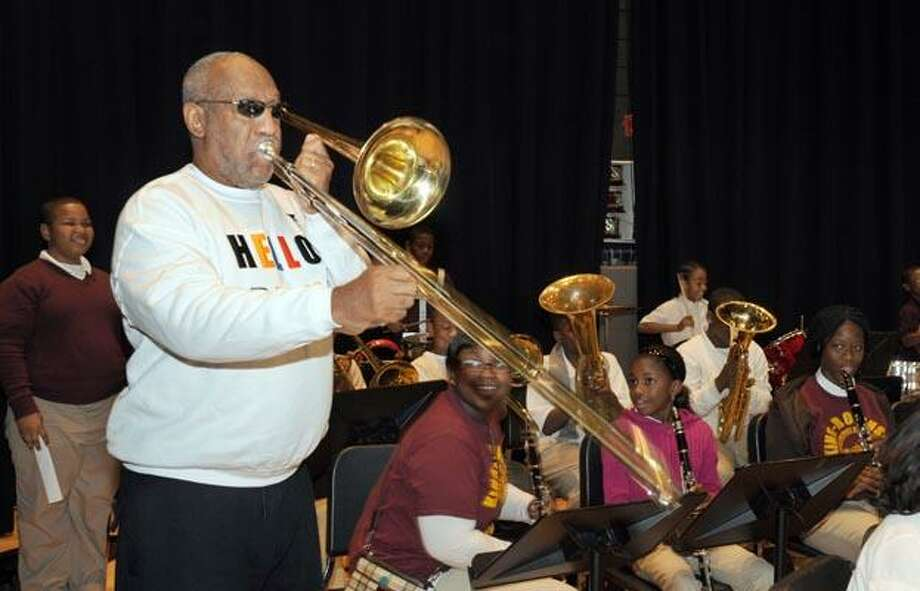 Comedian and educator Bill Cosby visited King/Robinson Interdistrict Magnet IB World School. He was brought to New Haven by SCSU president Stanley Battle. Here Cosby plays along with the school band by borrowing a student's instrument. Photo by Mara Lavitt/New Haven Register11/23/10