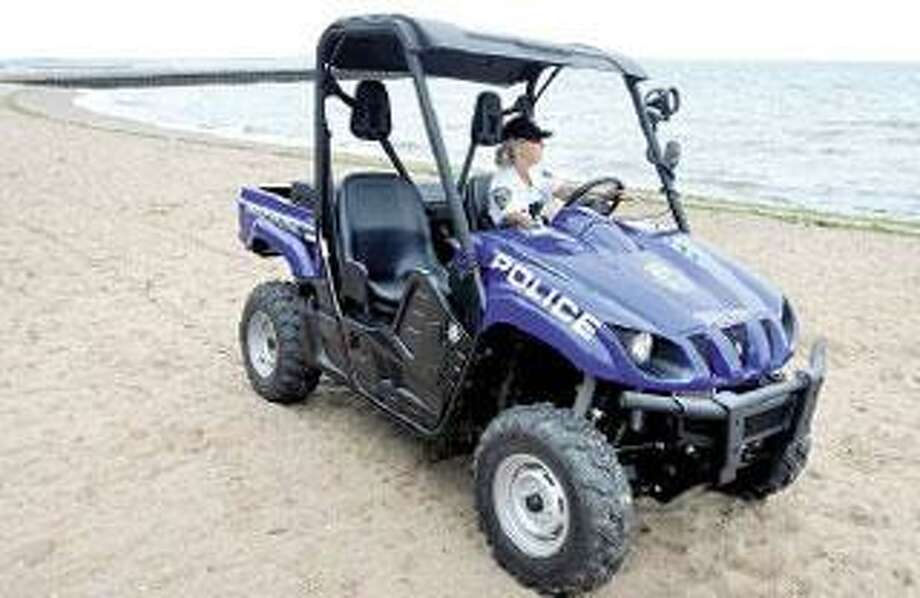 Patrol Officer Susan Carboni patrols a West Haven beach in the new police all-terrain vehicle. (Arnold Gold/Register)
