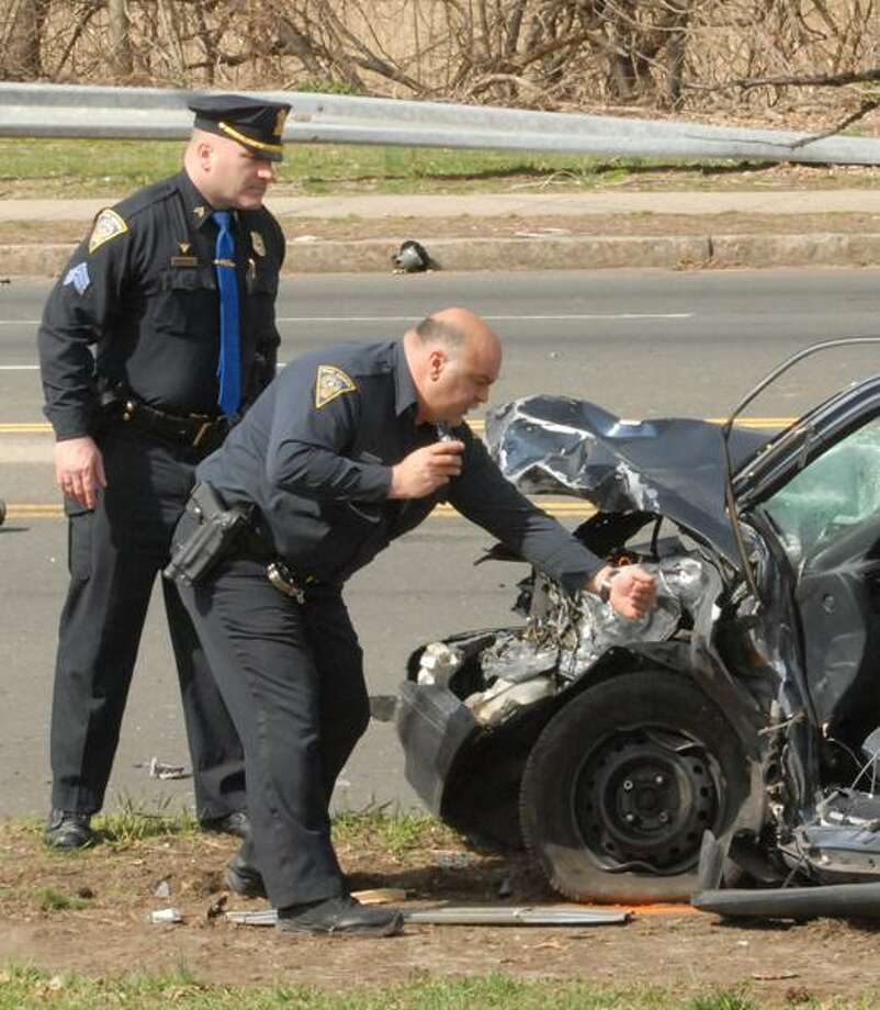 New Haven Police Accident Reconstruction Unit, left to right, Sargent John Magoveny and Officer William Coppola investigate a motor vehicle accident on Ella Grasso Boulevard near the corner of Derby Avenue on Thursday. Peter Hvizdak/Register Staff