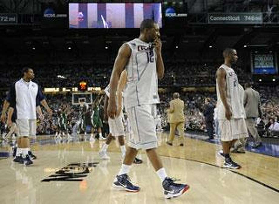 University of Connecticut basketball player A.J. Price, front, and his teammates walk dejectedly off the court after they lost to MSU. MSU beat UConn, 82-73. Photo taken on Saturday, April 4, 2009, at Ford Field in Detroit, Mich. (The Oakland Press/Jose Juarez)