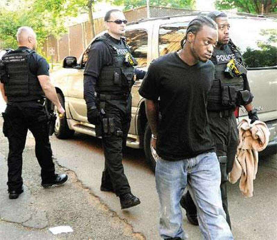 Duane Spence of New Haven is taken into custody by New Haven Detective Mike White after an early morning operation. Behind, from left, are Detective Carlos Maldonado and Sgt. Ray Johannes. (Melanie Stengel/Register)