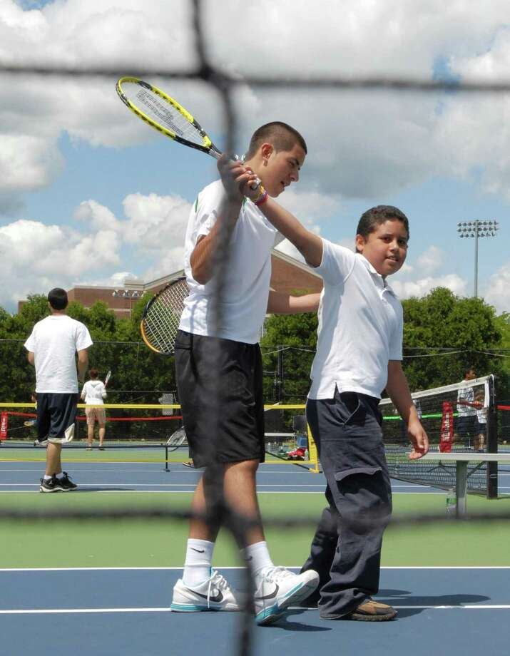 Photography by PETER HVIZDAK   ph2104     #2162New Haven, Connecticut- June 8, 2010:  Tennis player Giovanni Emestica of New Haven, 18, a Career High School senior and a member of the school's tennis team, left, teaches Juan Carlos Lopez, 8, of the 4th-grade at the Fair Haven School during  the annual Pilot Pen Tennis Tournament free tennis clinic for New Haven public school students from third to fifth grade . Emestica interest in tennis started at the tournament's clinic when he was in grade school.