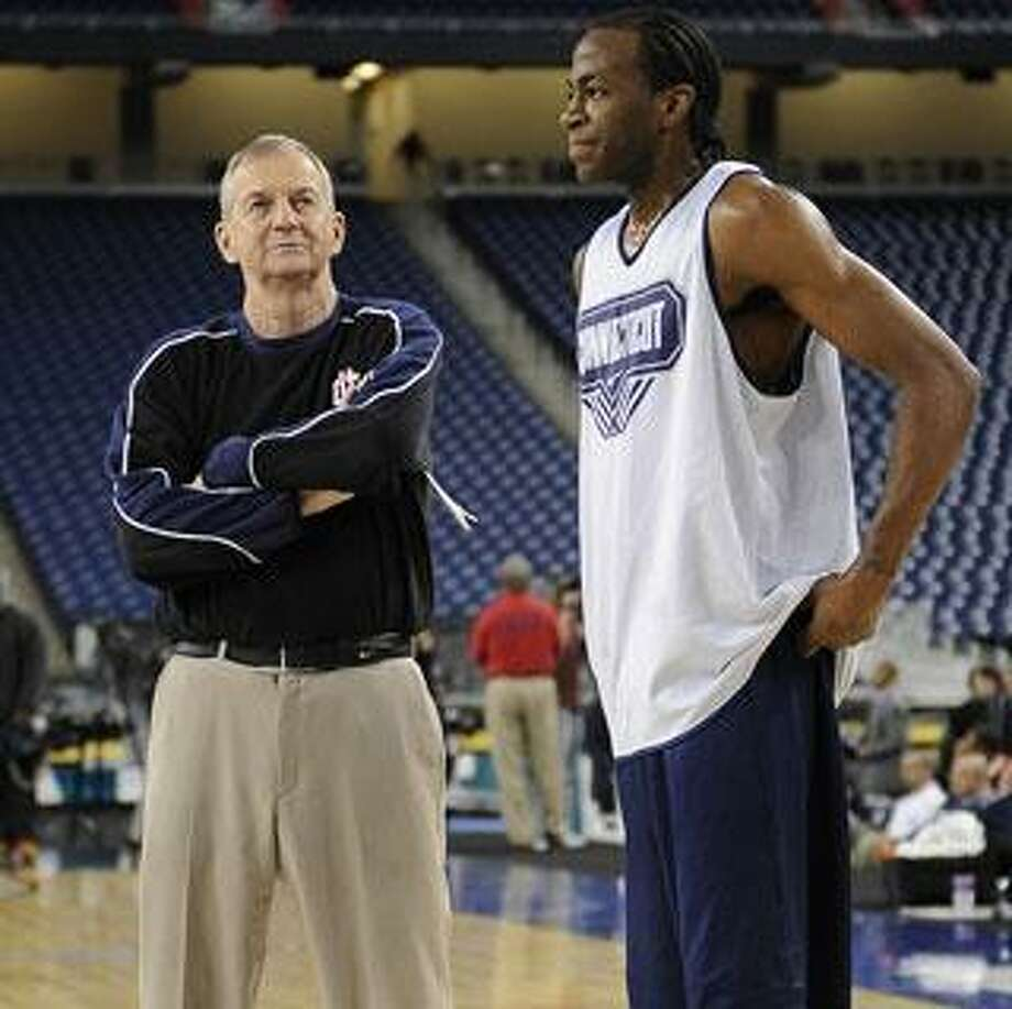 University of Connecticut basketball head coach Jim Cahoun, left, smiles next to player Stanley Robinson during team practice.  Photo taken on Friday, April 3, 2009, at Ford Field in Detroit, Mich.  (The Oakland Press/Jose Juarez)