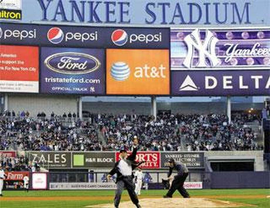 Former New York Yankees outfielder Reggie Jackson throws out the ceremonial first pitch Friday in the Yankees' first exhibition baseball game against the Chicago Cubs at the new Yankee Stadium. (Associated Press photos)
