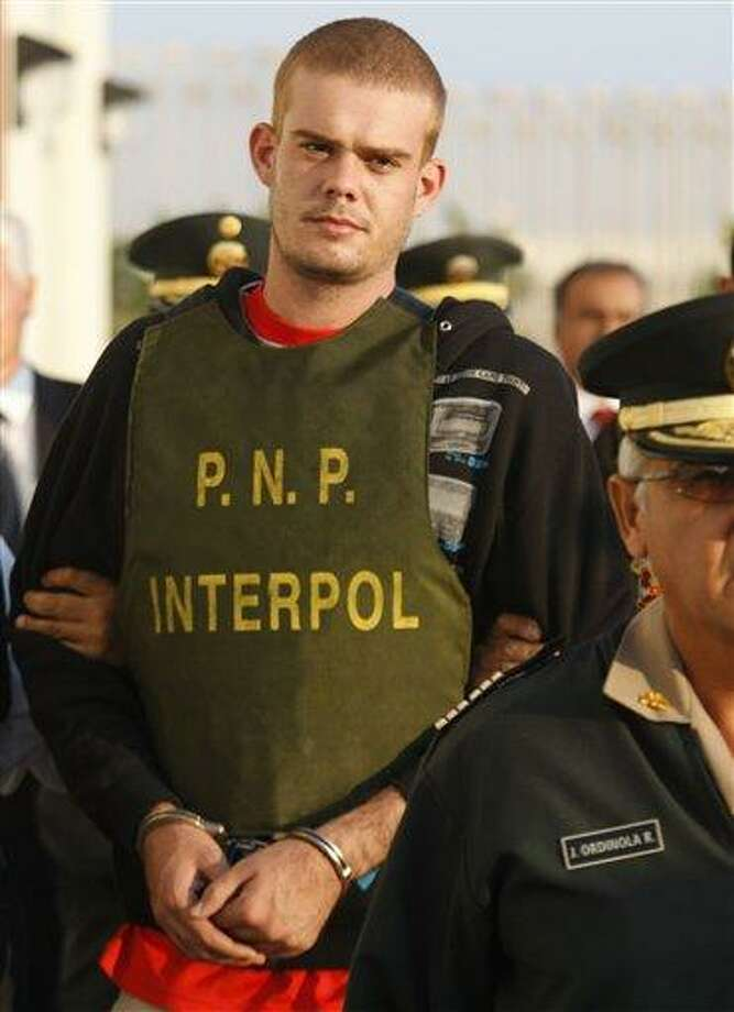 Dutch citizen Joran Van der Sloot, top, is escorted by police officers outside a Peruvian police station, near the border with Chile in Tacna, Peru, Friday, June 4, 2010. Chilean police have turned over van der Sloot, murder suspect in Sunday's killing of 21-year-old Stephany Flores, to Peruvian authorities at the countries' border. Van der Sloot was previously arrested in the 2005 disappearance of U.S. teen Natalee Holloway, but later released by Dutch authorities. (AP Photo/Karel Navarro) Photo: AP / AP