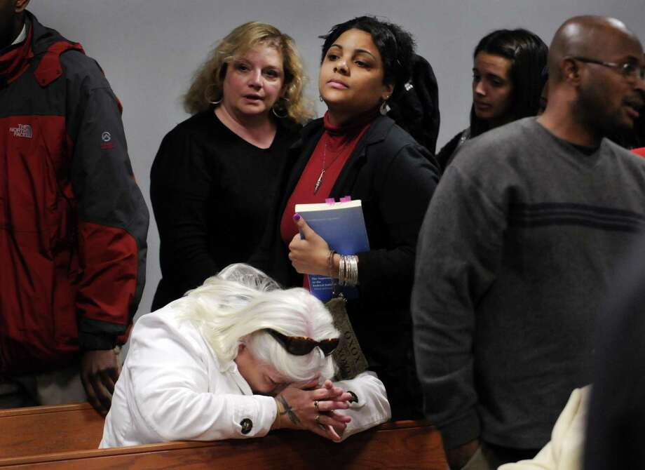 Mary Taylor, the wife of Ronald Taylor, sitting at left, breaks down after hearing the judge's ruling that her husband will be released after spending 16 years in prison, Wednesday, March 24, 2010, in Vernon, Conn. Taylor and George Gould were convicted of a 1993 New Haven murder, and their convictions were overturned last week. Behind Taylor is Ronald Taylor's daughter, Amanda Taylor, 21. At right is Christopher Gould, the brother of George Gould. (AP Photo/Stephen Dunn, Pool) Photo: AP / Pool Hartford Courant