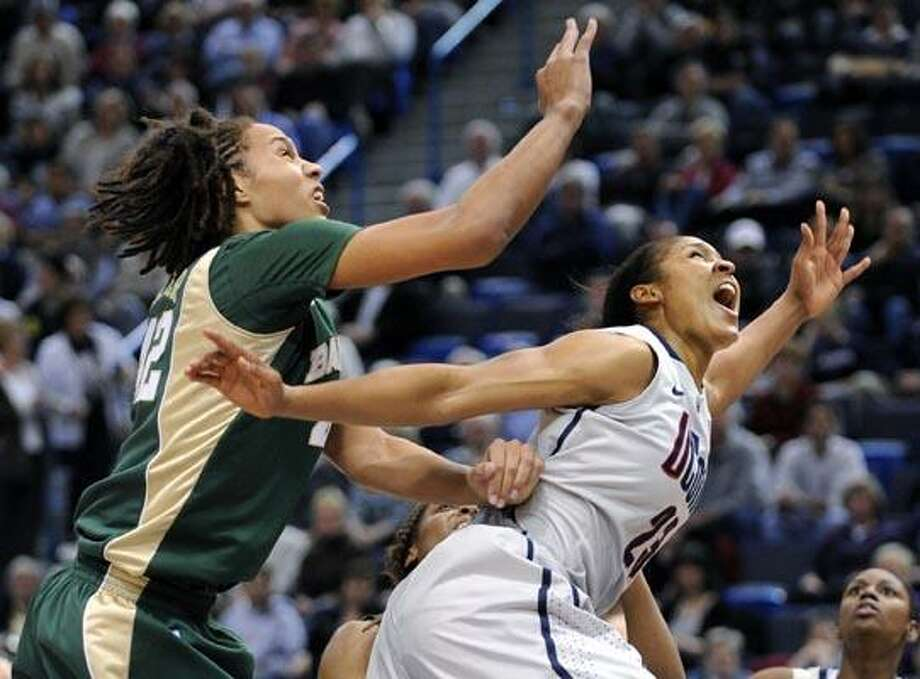 Connecticut's Maya Moore, right, and Baylor's Brittney Griner watch a shot by Moore during the first half of Connecticut's 65-64 victory in an NCAA college basketball game in Hartford, Conn., on Tuesday, Nov. 16, 2010. Moore scored a game-high 30 points and had seven rebounds. Griner scored 19 points, had seven rebounds and nine blocked shots. (AP Photo/Fred Beckham) Photo: AP / FR153656 AP