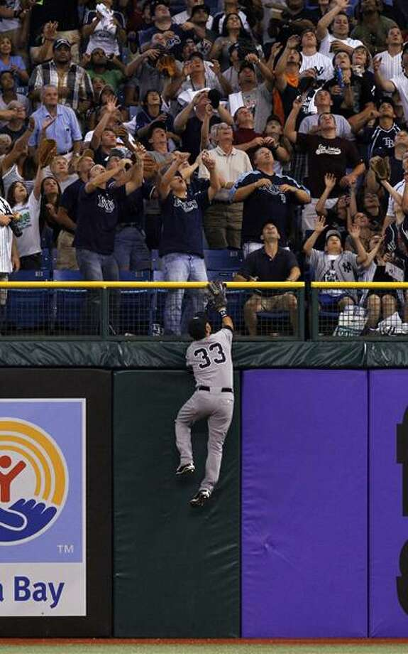 The Yankees' Nick Swisher climbs in vain as fans prepare to catch a home run ball off the bat of the Rays' Matt Joyce in the sixth inning of Tampa Bay's 3-2 win over New York Friday night in St. Petersburg. (Associated Press/Mike Carlson) Photo: AP / Mike Carlson Photography