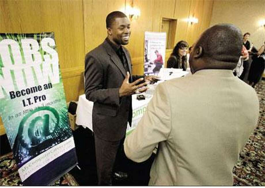 "Cedric James, left, admissions director with <a href=""http://MyComputerCareer.Com"">MyComputerCareer.Com</a>, meets with a prospective job applicant at a National Career Fairs Job Fair in Plano, Texas. New jobless claims fell last week for the third time in four weeks, but remain above 450,000, where they have been all year. (AP Photo)"