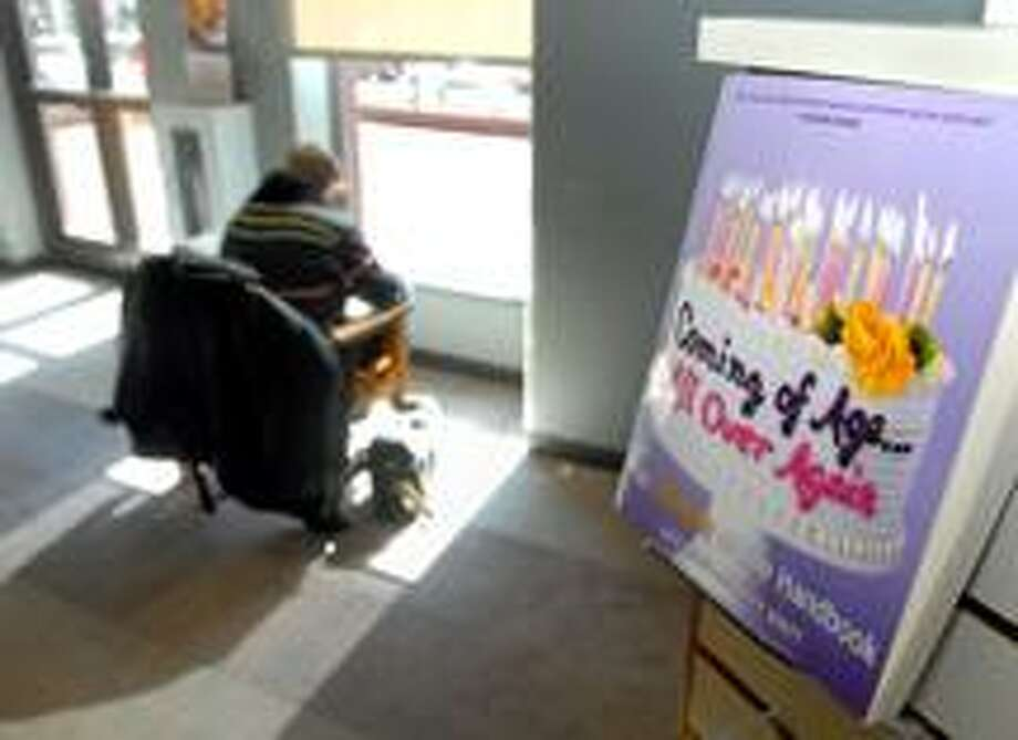 A patron reads at the 50+ Transition Center at the New Haven Public Library.  (Brad Horrigan/Register)