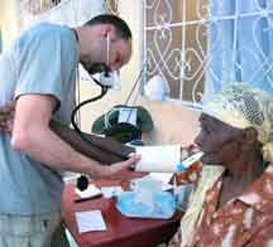 David Abromaitis, a New Haven resident and nurse at St. Mary's Hospital in Waterbury, examines a patient at the clinic in Marbial, Haiti. (Abbe Smith/Register)