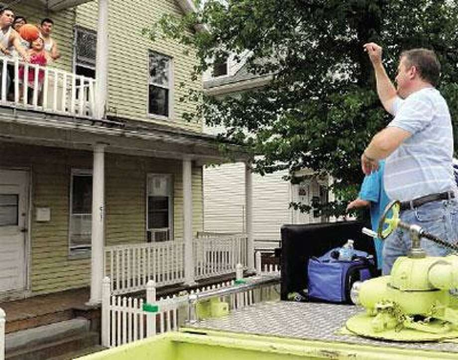 Kenneth Carney, owner of the West River Hall in West Haven, tosses a ball as he passes out all sorts of sports balls to Allingtown neighborhood children. (Mara Lavitt/Register)